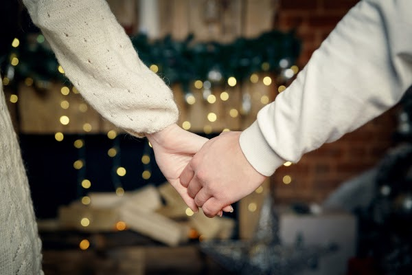 Couple holding hands in front of holiday fireplace